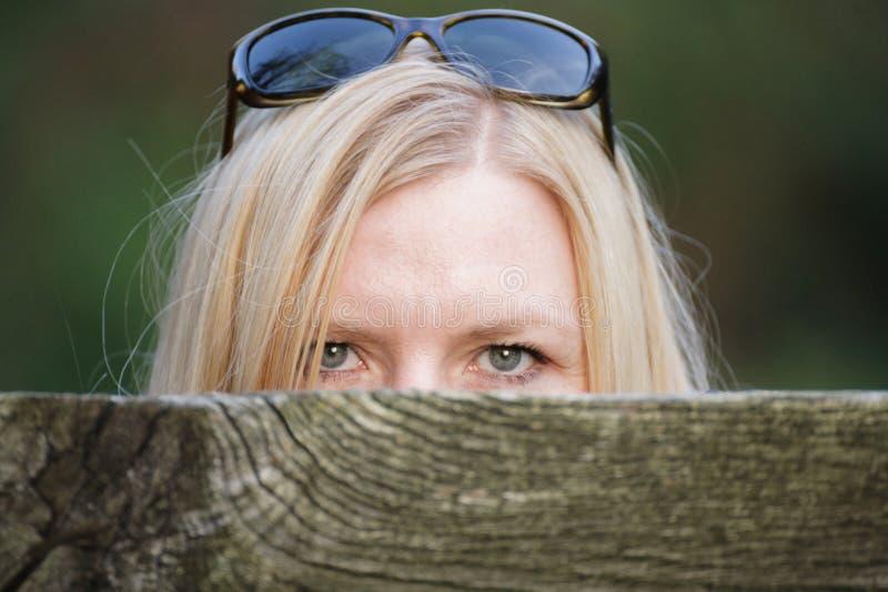 Besluipende vrouw achter een omheining die haar gezicht verbergen stock foto's