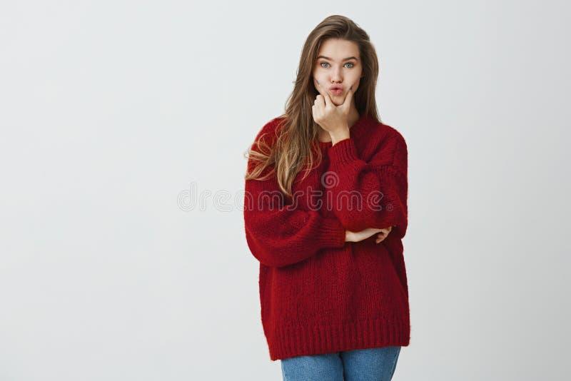 Besluiten die altijd verwarren Binnenschot van het charmeren van leuk wijfje in rode de wintersweater die lippen drukken en kijke royalty-vrije stock fotografie
