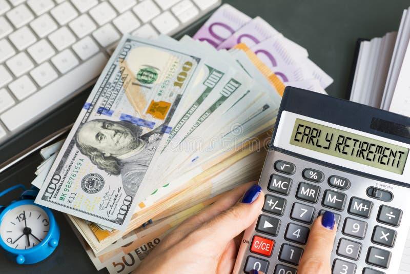 Beslut för tidig avgång med bunten av pengar på tabellen nära räknemaskinen och ringklockan arkivbilder