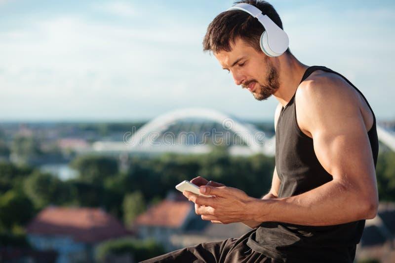 Beslutsam färdig ung man som använder en smart telefon som lyssnar till musik efter en genomkörare arkivfoton