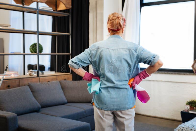 Beslutsam kvinna med bundet hår observera hennes lägenhet och planera royaltyfri bild