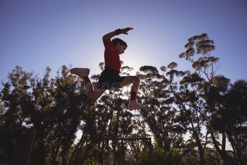 Beslutsam pojke som hoppar över hinder arkivbild