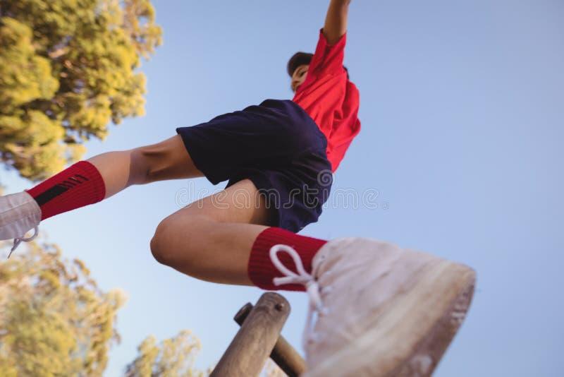 Beslutsam pojke som hoppar över hinder royaltyfri bild