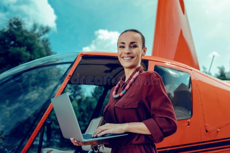 Beslutsam positiv kvinna med det breda leendet som bär den öppnade bärbara datorn royaltyfria bilder