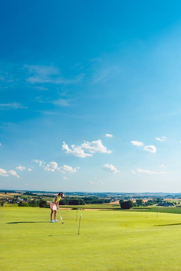 Beslutsam praktiserande golf för ung kvinna på gräset av ett utbildande område arkivfoto