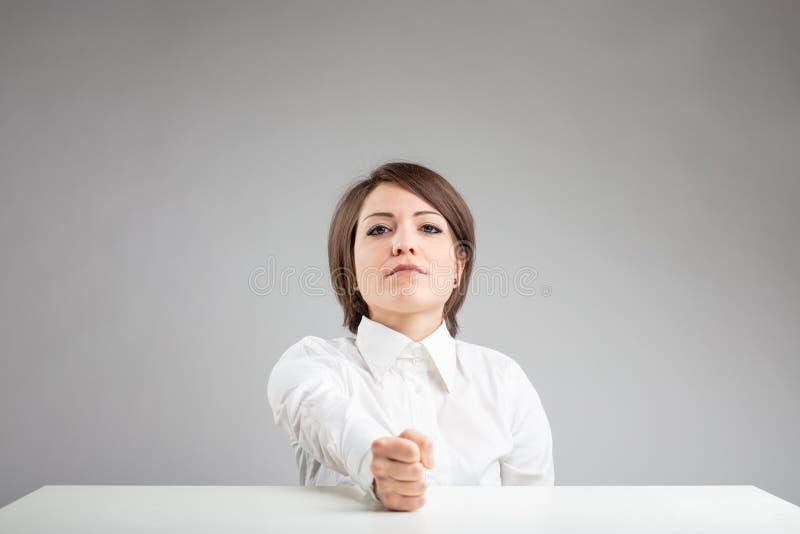 Beslutsam ung kvinna med hennes näve på tabellen royaltyfria foton