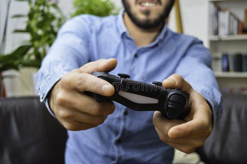 Beslutsam ung stilig maninnehavkontrollant och försöka hårt att segra på videospel royaltyfria foton