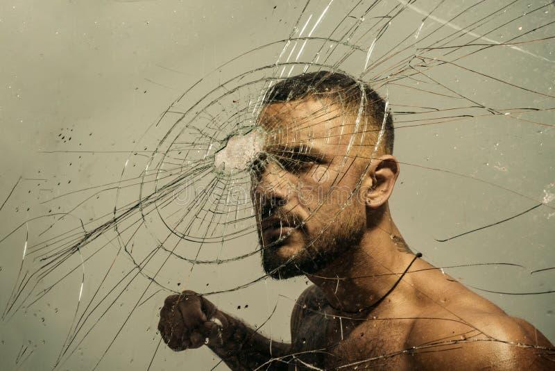 Beslutsamhet som lyckas Muskulös man som har inre beslutsamhet och förpliktelse för att bryta glasväggen Beslutsam latino arkivbild