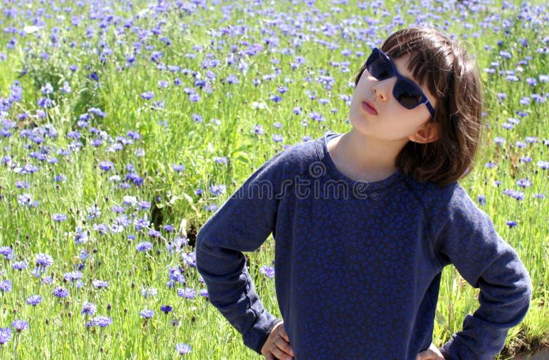 Beslutsamt barn med blå solglasögon som står över härligt blom- fält royaltyfri bild