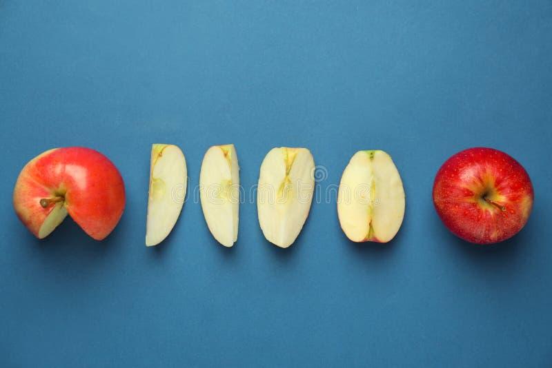 Besnoeiing en gehele rijpe verse appelen op kleurenachtergrond stock afbeelding