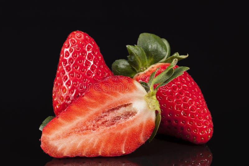 Besnoeiing en gehele verse vruchten van rode die aardbei op zwarte achtergrond wordt geïsoleerd royalty-vrije stock foto