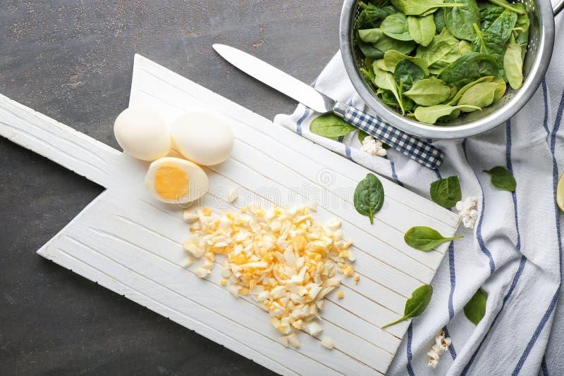 Besnoeiing gekookte eieren met spinazie op grijze lijst royalty-vrije stock foto's