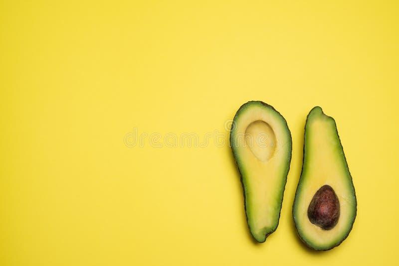 Besnoeiing in halve die avocado op gele achtergrond wordt geïsoleerd stock foto's