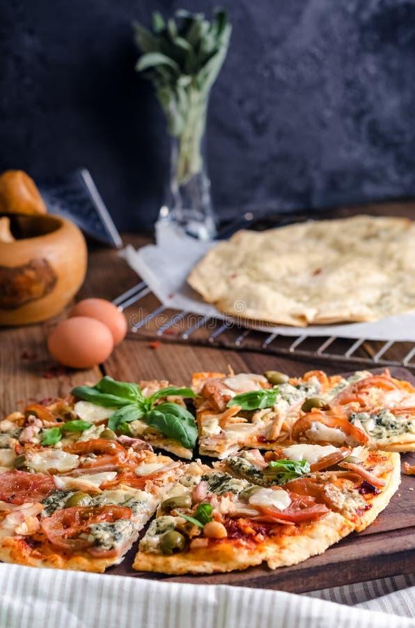 Besnoeiing in plakken heerlijke pizza op houten lijst stock afbeeldingen