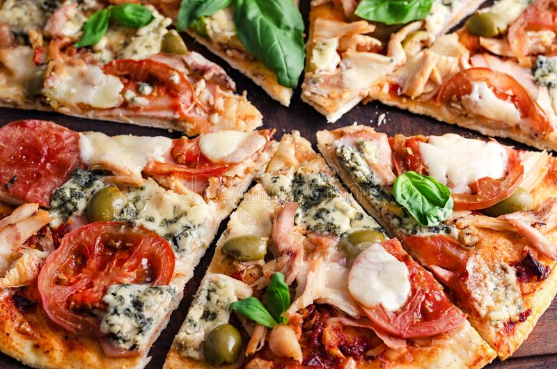 Besnoeiing in plakken heerlijke pizza op houten lijst stock fotografie