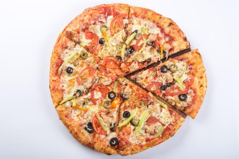 Besnoeiing in stukken van pizza met vlees, olijven en paddestoelen op een houten schotel stock foto's