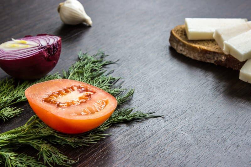 Besnoeiings rood uien, tomaat, dille, reuzelsalo en knoflook op houten lijst royalty-vrije stock afbeeldingen