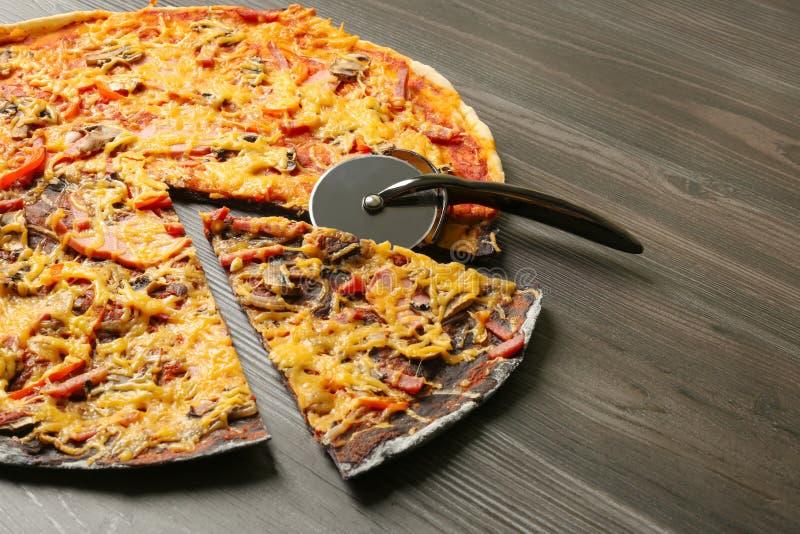 Besnoeiings zwart-witte pizza met mes op houten lijst, close-up stock fotografie
