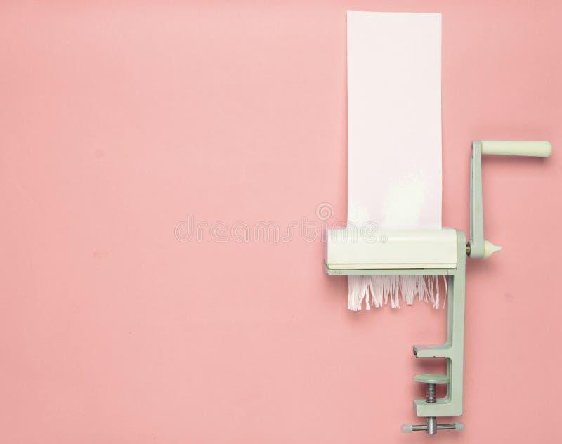 Besnoeiingsdocument door een handmachine om deegwaren op een blauwe pastelkleur te snijden royalty-vrije stock afbeelding