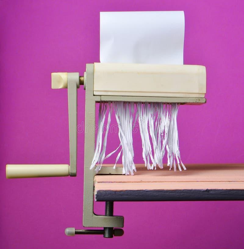Besnoeiingsdocument door een handmachine om deegwaren op een roze pastelkleurachtergrond te snijden, minimalistische tendens, ret stock foto's