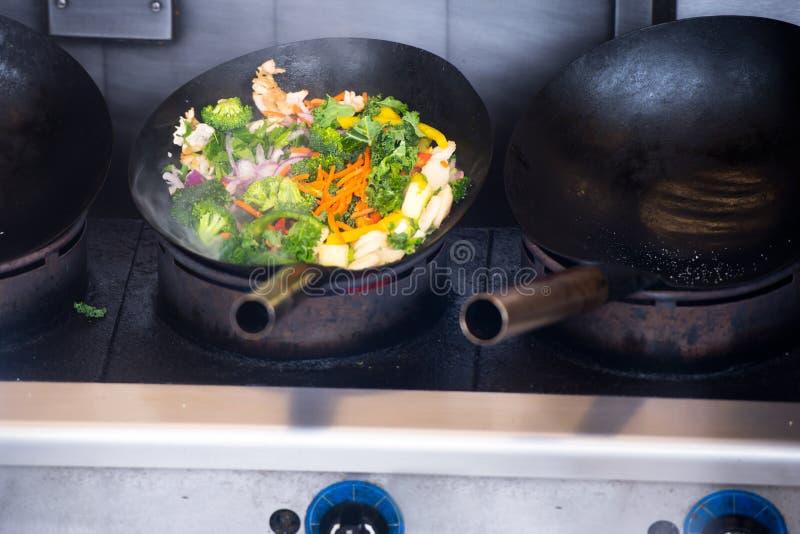 Besnoeiingsgroenten in een pan op een groot industrieel fornuis worden gestoofd dat stock afbeeldingen