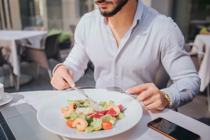 Besnoeiingsmening van gebaarde jonge mensenzitting bij lijst en het eten van salade Er zijn laptop en telefoon op beeld royalty-vrije stock afbeelding