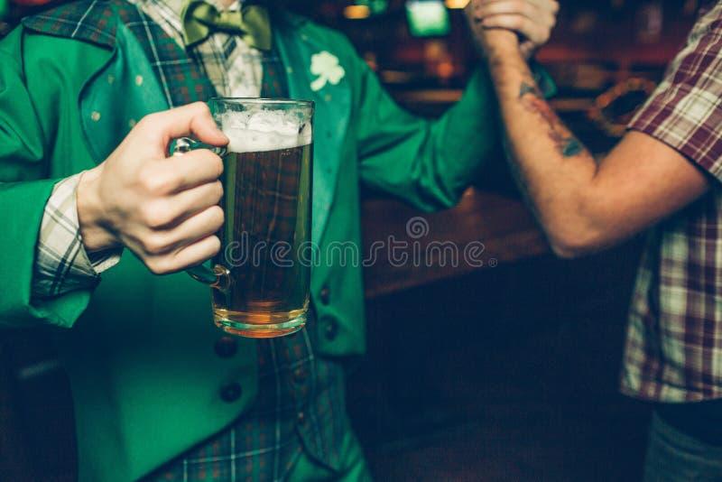 Besnoeiingsmening van twee mensen die elkaars handen houden De kerel in groen kostuum heeft mok bier Zij bevinden zich binnen in  royalty-vrije stock afbeeldingen