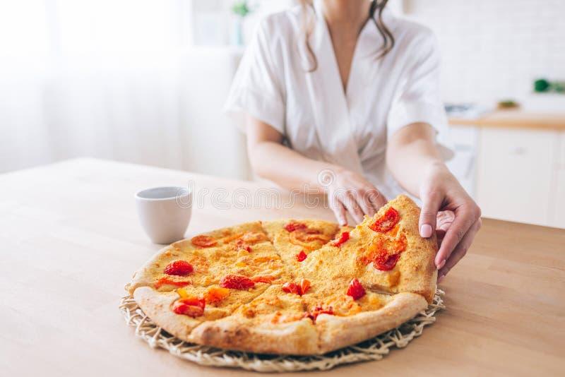 Besnoeiingsmening van vrouw in witte peignoir in keuken Het nemen van stuk van pizza Kleine plak Jonge huishoudster levende onbez royalty-vrije stock foto's