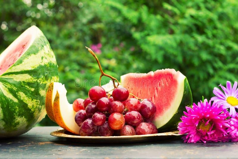 Besnoeiingsplakken van rijpe gele meloen, watermeloen, een bos van druiven en bloemenasters op een lijst met natuurlijke groene a royalty-vrije stock fotografie