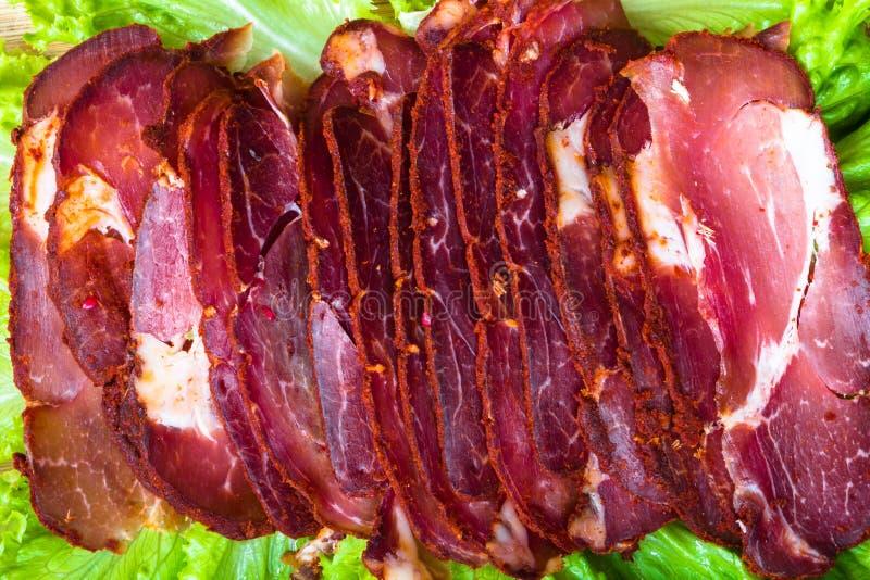Besnoeiingsstukken van gerookt vlees met sla en peper stock afbeeldingen