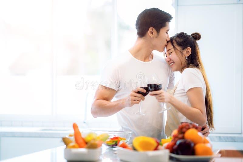 Beso asiático de los pares en cocina imagen de archivo
