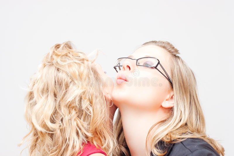 Beso de la mejilla de las mujeres imagen de archivo