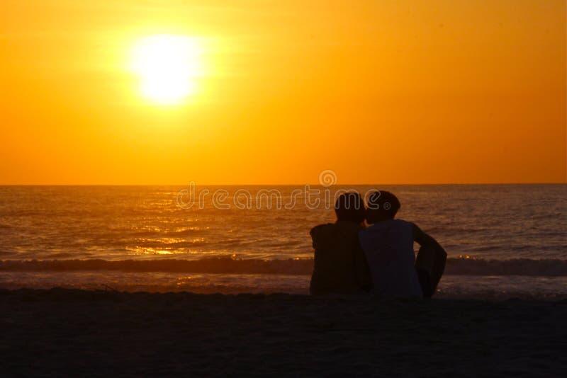 Beso de la salida del sol de la silueta en la playa fotografía de archivo