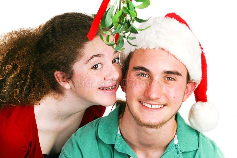 Beso del muérdago de la Navidad - adolescencias fotografía de archivo