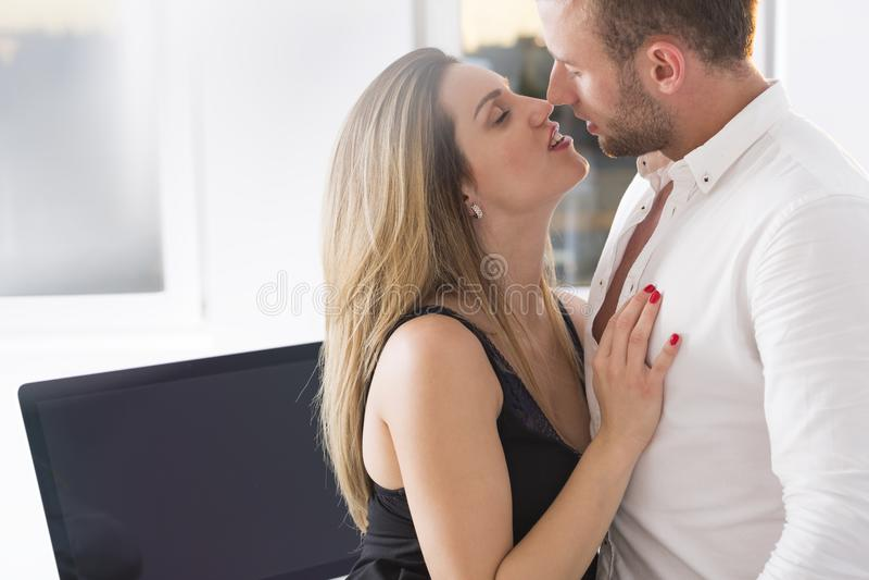 Beso sensual en el trabajo fotografía de archivo