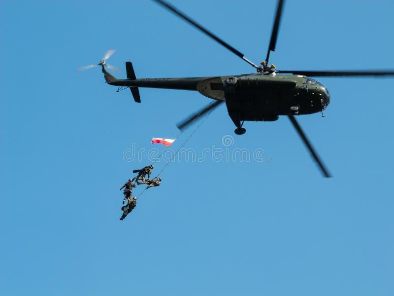 Besondere Kräfte GROM, die an den Seilen von einem Hubschrauber hängen lizenzfreie stockbilder