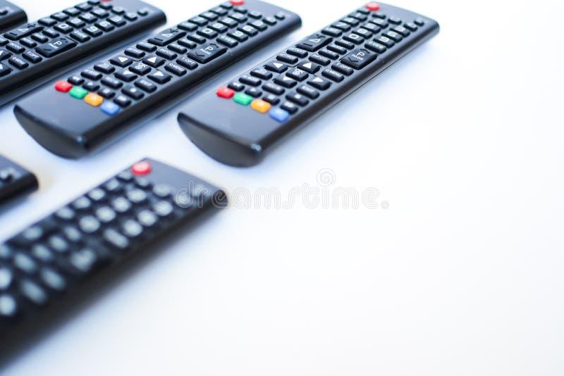 Besonders schwer unscharfe schwarze Fernbedienungen für das Fernsehen auf einem weißen Hintergrund lizenzfreie stockfotografie