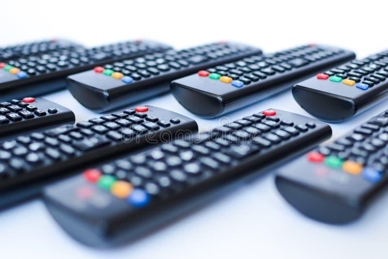 Besonders schwer unscharfe schwarze Fernbedienungen für das Fernsehen auf einem weißen Hintergrund lizenzfreie stockfotos