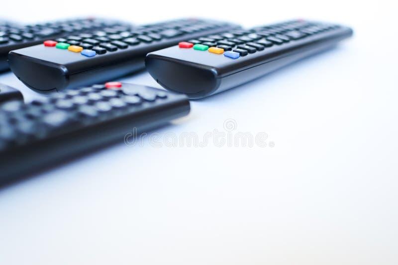 Besonders schwer unscharfe schwarze Fernbedienungen für das Fernsehen auf einem weißen Hintergrund lizenzfreies stockbild