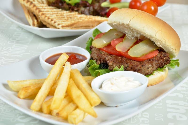 Besonders zugebereiteter Hamburger und Pommes-Frites stockfotografie