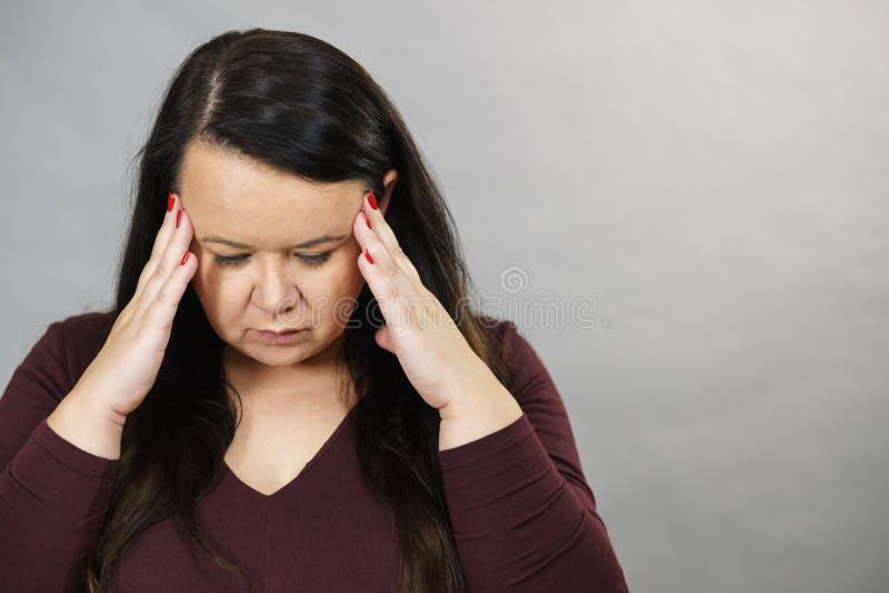 Besorgnis erregende Frau mit schmerzhaften Kopfschmerzen lizenzfreie stockfotos