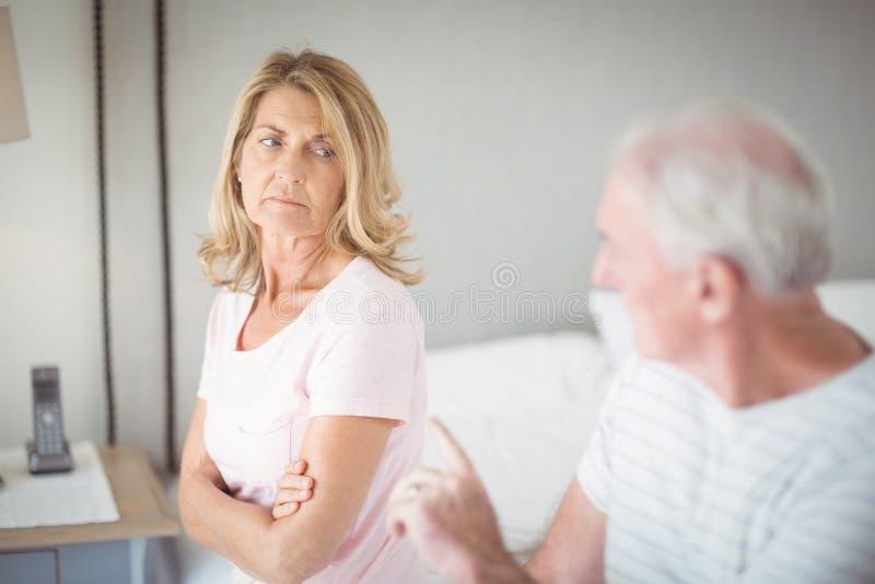 Besorgte ältere Frau, die auf Bett sitzt lizenzfreies stockfoto