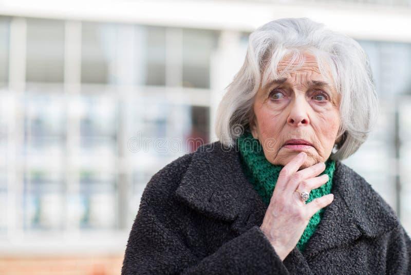 Besorgte ältere Frau, die draußen verloren schaut lizenzfreies stockbild