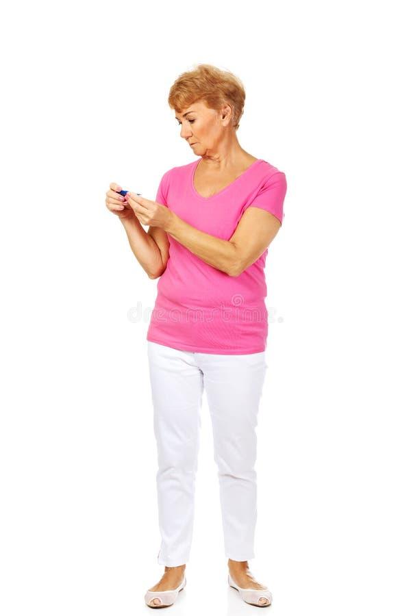 Besorgte ältere Frau, die nach Thermometer sucht stockfotografie