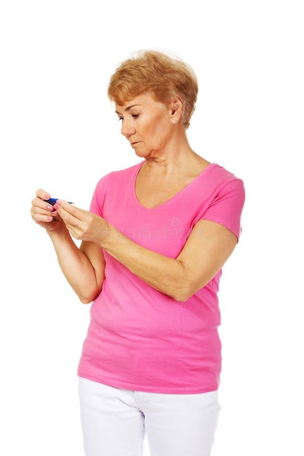 Besorgte ältere Frau, die nach Thermometer sucht lizenzfreie stockfotografie