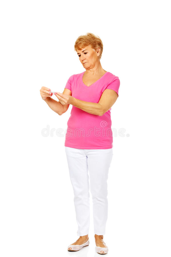 Besorgte ältere Frau, die Thermometer hält stockbild