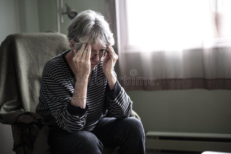 Besorgte ältere Frau zu Hause, die sehr schlechtes fällt lizenzfreies stockfoto