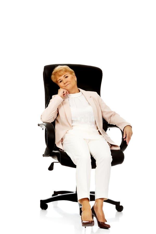 Besorgte ältere Geschäftsfrau, die auf Lehnsessel sitzt stockfotografie