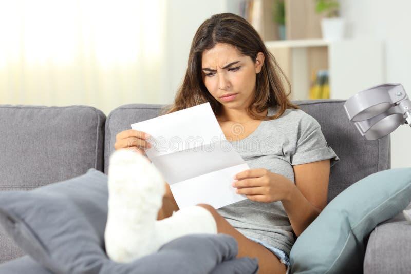 Besorgte behinderte Frau, die einen Brief liest lizenzfreie stockfotografie