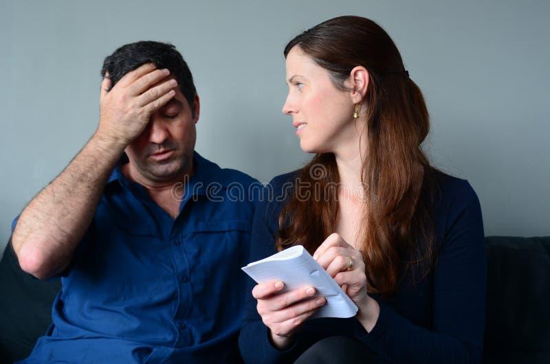Besorgte Ehemann- und Frauauflistungsausgaben lizenzfreie stockfotos